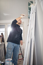 Young Adult Man Painting On A DIY Budget Renovation Of His New Home Apartment.
