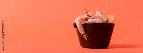 Foto Shrimps with lemon and fresh dill in a small black bowl over colorful background