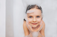 A Little Girl With Long Hair, The Child Is Washed, Sitting In A White Bath With Foam From Soap, Shampoo. Model Photography. Face Close-up.