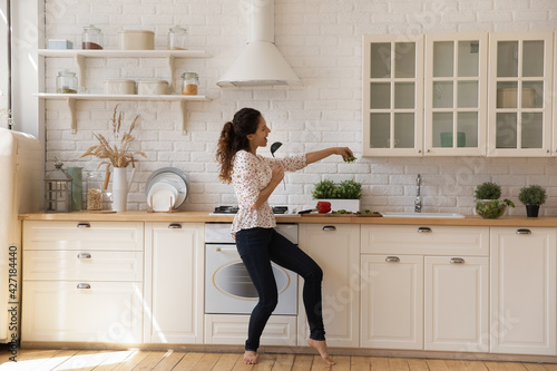 Foto Funny young woman dancing in modern kitchen at home, singing in kitchenware and