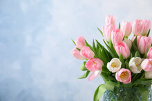 Beautiful Bouquet Of Tulips In Glass Vase Against Light Background. Space For Text