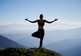 Silhouette of woman practicing yoga on background of evening mountains. Meditating female is balancing on one leg after sunset. Concept of yoga.