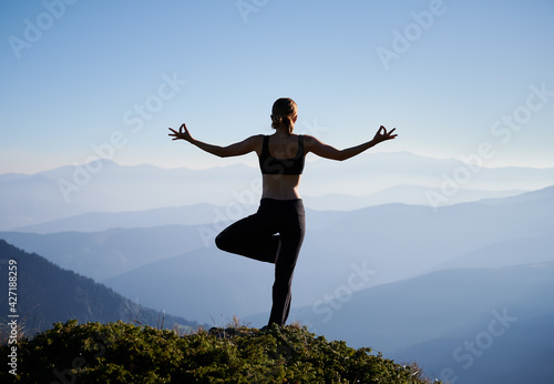 Fototapeta Silhouette of woman practicing yoga on background of evening mountains. Meditating female is balancing on one leg after sunset. Concept of yoga. obraz