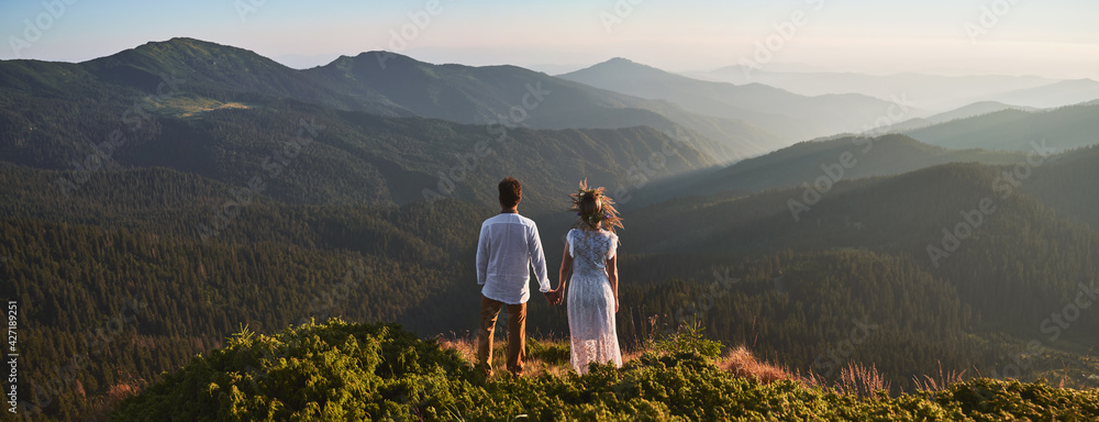 Fototapeta Back view of loving couple standing on grassy hill and holding hands while looking at beautiful mountains. Young man holding hand of charming woman in white dress and admiring beauty of nature.