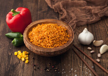 Wooden Bowl With Boiled Red Long Grain Basmati Rice With Vegetables On Wooden Table Background With Sticks And Red Paprika With Corn,garlic And Basil.