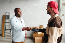 Young Loader In Workwear Holding Terminal While African Male Client Paying For Loading And Delivering Service By Credit Card