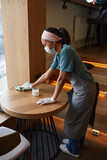 Vertical high angle portrait of young African-American woman wearing mask while cleaning tables with sanitizer at cafe or coffee shop, covid safety measures