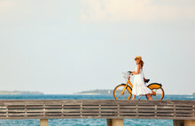 Woman Walking With Bicycle Along Promenade