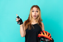 Young Cyclist Girl Over Isolated Blue Background Surprised And Pointing Finger To The Side