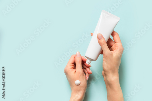 Fotografiet Beauty concept with woman hand and cream tube on blue background