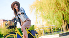 Smiling Woman In Denim Jacket And Straw Hat Riding Rental Bicycle Outdoors In Public Park