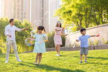 Happy Young Family Blowing Bubbles On Grass