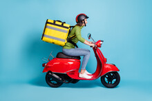 Full Length Side Profile Photo Portrait Of Woman Delivering Big Yellow Package On Red Scooter Isolated On Pastel Blue Colored Background