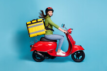 Full Length Photo Portrait Of Woman Delivering Big Yellow Package On Red Scooter Isolated On Pastel Blue Colored Background