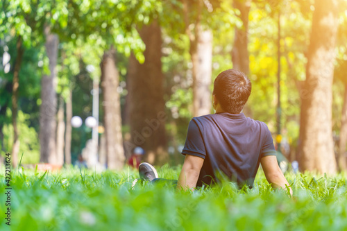 young asian man sitting on green grass and listening to music with earphones from mobile smart phone outdoors