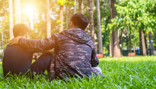 Two Asian Man Friends Sitting On Green Grass In The Park, Encouraging, Comforting His Friend And Looking In The Same Direction