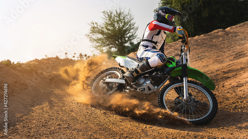 Photographie Young man practice riding dirt bike.Splashing sand