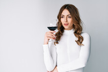 Pretty Fashion Woman Holding Glass Of Red Wine On White Background With Copy Space