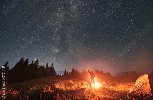 Fototapeta Silhouette of man hiker near campfire, pointing finger at beautiful night starry sky with Milky Way under mountain valley with tourist tent