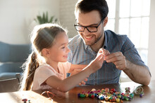 Playful Young Caucasian Father And Little Happy Daughter Have Fun Making Bracelets Accessories At Home Together. Loving Dad And Small Girl Child Engaged In Funny Hobby Creative Activity String Beads.
