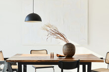 Minimalist Composition Of Dining Room Interior With Wooden Table, Design Chairs, Dried Flowers In A Vase, Black Pendant Lamp, Art Paintings On The Wall And Elegant Personal Accessories. Template.