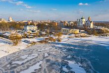 Nice Top View Of The Winter City. Houses And Buildings In The Snow. Bridge Over River. Orthodox Churches And A Catholic Cathedral. The River Is Covered With Ice.