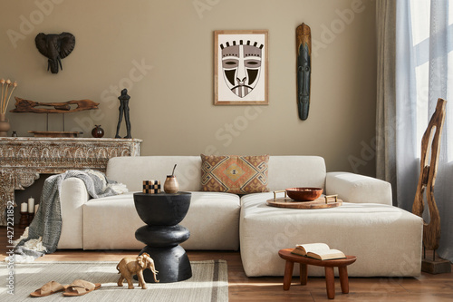 Stylish ethnic living room interior with design sofa, wooden stool, moroccan shelf, carpet decor, a lof of decoration and elegant personal accessories. Template.