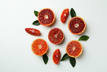 Red Orange Slices With Leaves On White Background, Top View