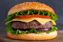 Fresh Delicious Homemade Burger With Juicy Meat, Tomatoes, Onions, Cheese And Salad On A Dark Stone Background With Copy Space On A Wooden Board. Side View. Fast Food. Close-up. Free Space For Text