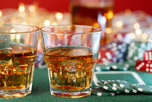 Game Chips Lie Next To Dice And Glass Of Whiskey