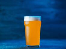 New England IPA Craft Beer Glass On Dark Blue Background