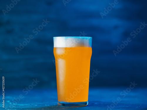фотография New England IPA craft beer glass on dark blue background