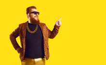 Happy Smiling Redhead Man With Ginger Beard And Mustache, In Sunglasses, Funny Leopard Jacket And Gold Chain Necklace Standing On Amber Yellow Background Pointing Finger To Free Advertising Text Space