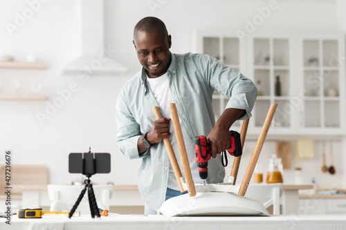 African american handyman shooting video how to adjusting or assembling chair, recording online instructions on phone