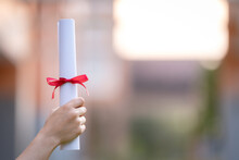 Close-up Shot Of A University Graduate Holding A Degree Certification To Shows And Celebrate Education Success On The College Commencement Day. Education Stock Photo