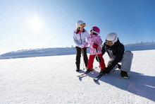Young Parents Teaching Daughter To Ski