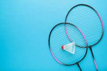 Shuttlecocks And Badminton Racket On Blue Background. Badminton Equipment With Copy Space