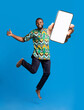 canvas print picture Positive black man in traditional colorful costume jumping up with empty cellphone over blue studio background, mockup