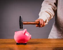 Hand With A Hammer Breaks A Piggy Bank. Save Money,  Concept
