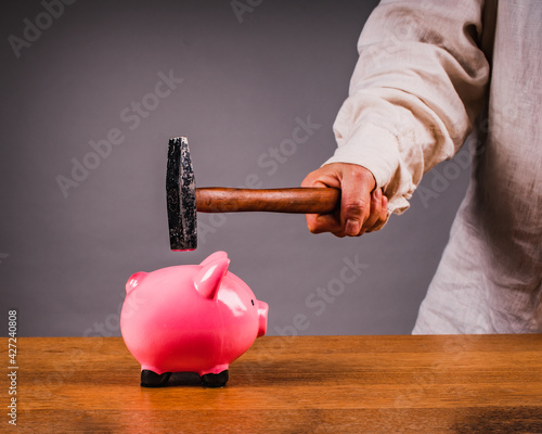 Photo Hand with a hammer breaks a piggy bank. Save money,  concept