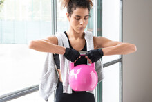 Close Up Of Young Beautiful Woman Doing Crossfit Russian Swing In A Gym With A Pink Kettlebell. Horizontal View