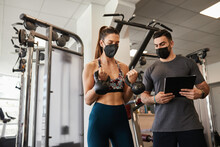 Personal Trainer And Fit Woman Training Wearing Face Masks During Pandemic