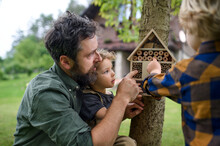 Small Children With Father Holding Bug And Insect Hotel In Garden, Sustainable Lifestyle.