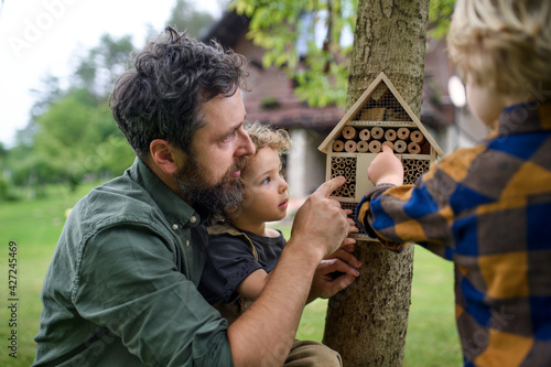 Tablou Canvas Small children with father holding bug and insect hotel in garden, sustainable lifestyle