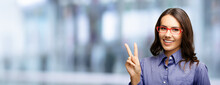 Happy Smiling Beautiful Business Woman In Red Glasses Showing Two Fingers Or Victory Hand Sign Gesture, Over Blurred Modern Office Interior Background.