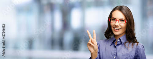 Photo Happy smiling beautiful business woman in red glasses showing two fingers or victory hand sign gesture, over blurred modern office interior background