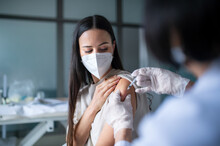 Woman With Face Mask Getting Vaccinated In Hospital, Coronavirus And Vaccination Concept.