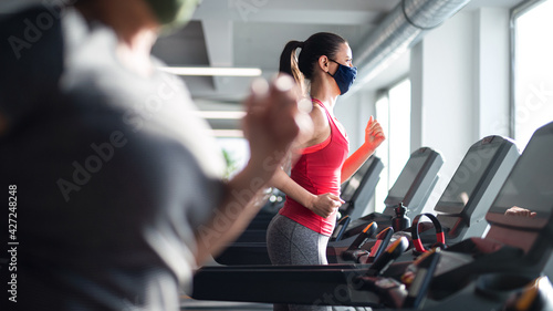 Woman with face mask doing exercise on treadmill in gym, coronavirus concept.
