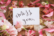 MISS YOU Card On A Wooden Table Between Pink Flowers