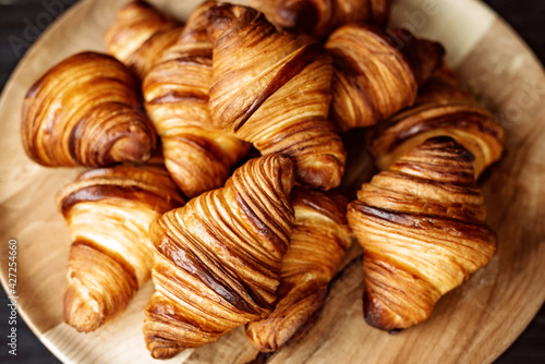 Fototapeta Fresh baked croissants. Warm fragrant butter croissants and rolls on a wooden stand. French and American pastries are popular all over the world. obraz